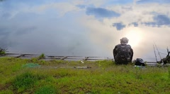 Fisherman on the shore of the lake, the view from the back, the sky reflected in - stock footage