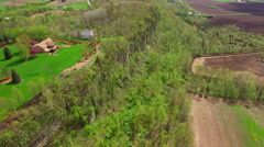 High rocky cliff separates neighborhood from farm land far below - stock footage