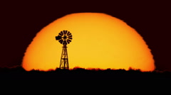 Silhouette of farm windmill in the blazing heat of a late summer sun. Stock Footage