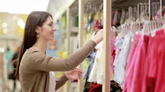Young woman chooses clothes for newborn baby Stock Footage