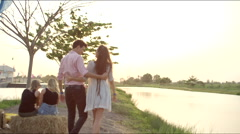 A couple walks towards the sunset - stock footage