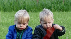 Twins with an appetite eating the treat candy caucasian sitting on the grass - stock footage