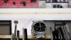 Hockey team's equipment lying on bench, empty ice rink, popular winter sport Stock Footage