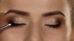 Eye makeup woman applying eyeshadow powder. Beautiful woman face. Closeup Stock Footage