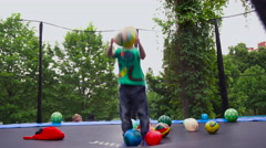 Child Jumping on a Trampoline With Balls Stock Footage