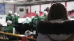 Back view of hockey fans and teammates actively supporting players on ice rink Stock Footage