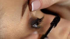 Woman applying mascara on her long eyelashes. Black. Closeup Stock Footage
