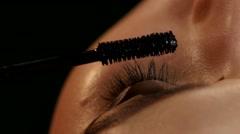 Makeup artist applying mascara. Black. Closeup Stock Footage