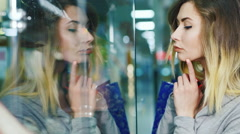 Attractive woman considering a shop window. In the window you see her reflection - stock footage