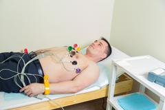 Male patient having ECG electrocardiogram in hospital - stock photo