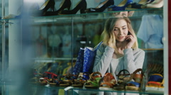Attractive woman talking on the phone in the glass showcases shoe store - stock footage