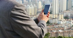 4k business man using a smartphone aganist modern urban building background. Stock Footage
