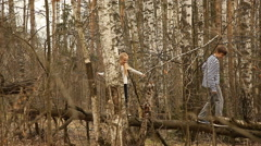 Boy and girl go on a log in the autumn forest Stock Footage