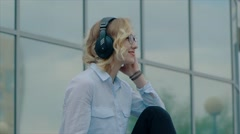 Smiling young blond woman standing outside with headphones - stock footage