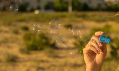 Bubbles at the sky, romantic inflating colorful soap bubbles in park. - stock photo