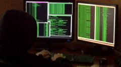 Criminal hacker with black hood penetrating network system from his dark room. Stock Footage