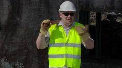 Angry Construction worker with sledgehammer talking near wall - stock footage