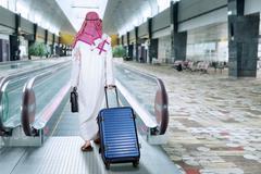 Arabic businessman walks in escalator - stock photo