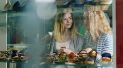 Two young women looking at a glass case a shoe store - stock footage