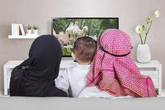 Arabic family watching television at home Kuvituskuvat