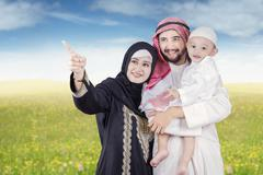 Arabic parents and their son look at something - stock photo