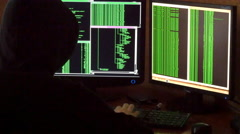 Hacker breaking code. Criminal hacker with black hood penetrating network system Stock Footage