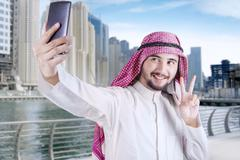 Arabic person taking selfie in the city - stock photo