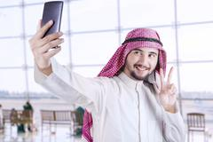 Arabic tourist taking selfie in the airport Stock Photos