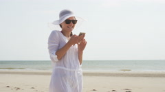 4K Attractive young woman on the beach using her phone Stock Footage