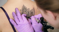 Woman tattoo master is making tattoo flower on the woman's back, close up Stock Footage