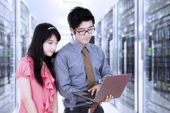 Asian workers working in server room Kuvituskuvat