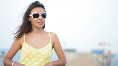 Woman in sunglasses posing on the pontoon near sea Stock Footage