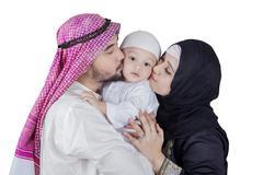 Two Arabic parents kiss their son - stock photo
