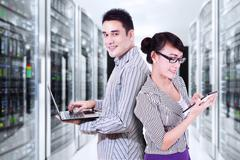 Two businesspeople working in server room Kuvituskuvat