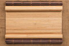 Two bamboo mat twisted in the form of a manuscript on sackcloth - stock photo