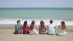 Six young people sitting overlooking the ocean Stock Footage