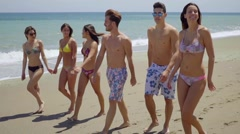 Group of multiracial young friends on a beach Stock Footage