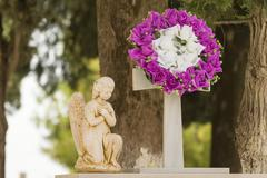 Flower garland and a statue on a grave after a funeral. Stock Photos