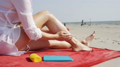 4K Young woman applying sun cream to her legs on the beach, in slow motion Stock Footage