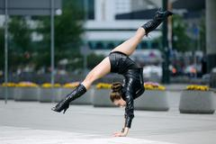 Beautiful woman performing acrobatics in the city - stock photo
