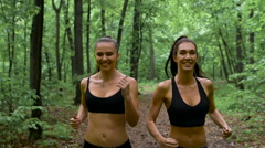 Fitness workout outdoors. Two slender brunette with long hair running through Stock Footage