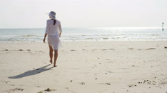 4K Attractive young woman walking along a sandy beach, in slow motion Stock Footage