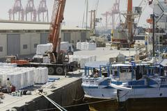 Large harbour crane loading cargo on a vessel at the Port of Salalah Stock Photos