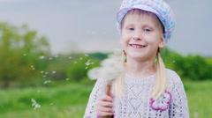 Girl 5 years old playing with dandelions Stock Footage