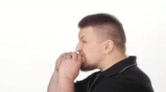 Young man eating fast food. White Stock Footage