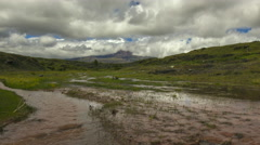 Time-lapse of muddy floodwater running over the paramo.  Stock Footage