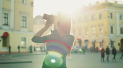 Young female taking pictures of an old town slow motion Stock Footage