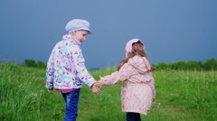 Two girls 5 and 3 years running away into the distance on a country road Stock Footage