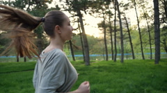 Young woman runs in park slow motion Stock Footage
