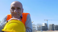 Pensive Old Worker with his yellow helmet Stock Footage